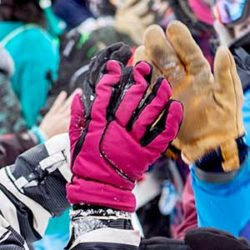 Two people in winter mountain gear high-fiving