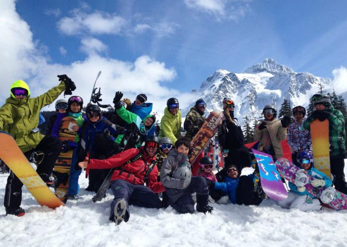 SOS Outreach youth posing in front of a mountain with skis and snowboards