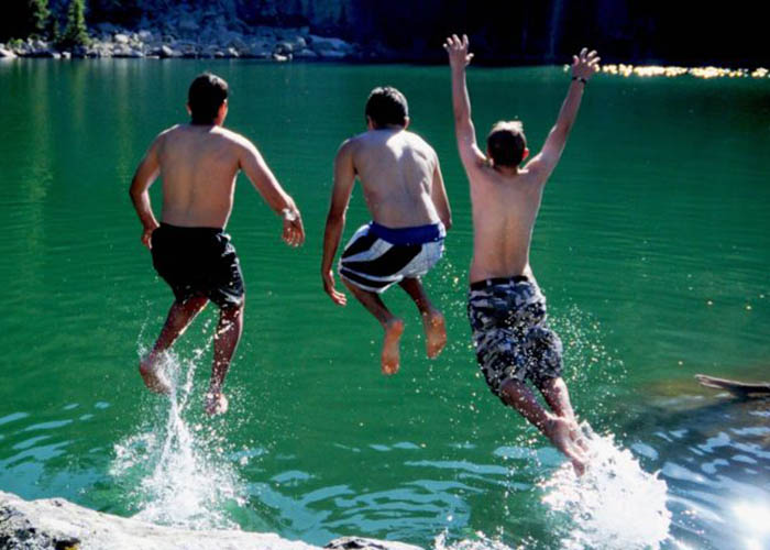 SOS Outreach youth jumping into the water during summer