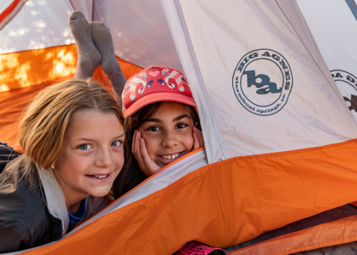 Two kids camping in a Big Agnes tent at an SOS Outreach event