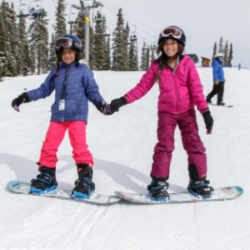 Friends holding hands while snowboarding with SOS Outreach